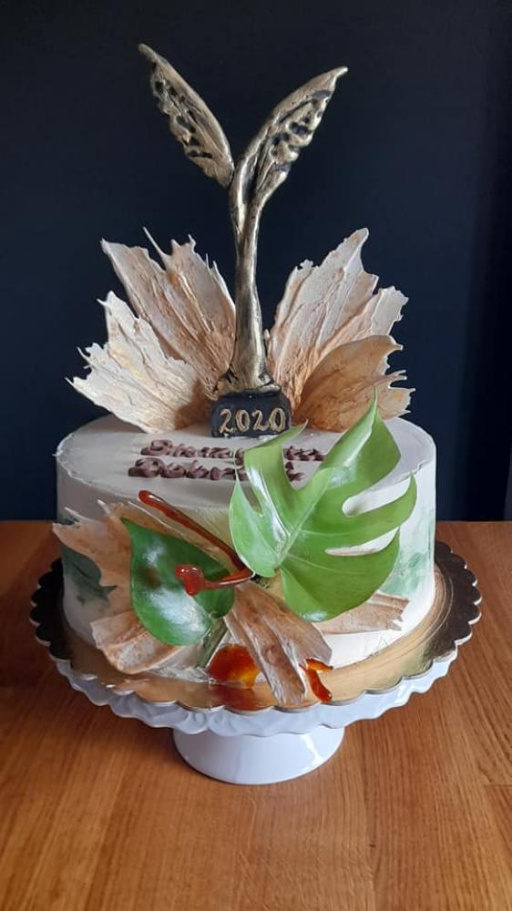 Tort. Zdjęcie przedstawia artystycznie wykonany tort, przygotowany dla członków  Klubu Seniora.  Na torcie umieszczona jest statuetka