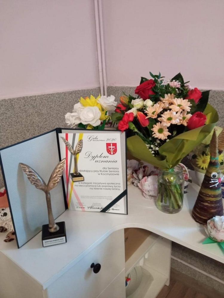 Zdjęcie przedstawia  statuetkę, dyplom uznania oraz bukiet kwiatów.