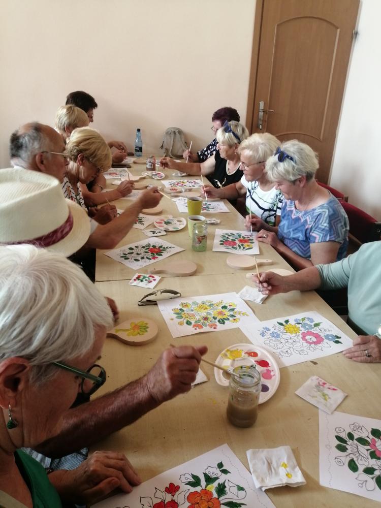 na zdjęciu znajdują się kobiety i mężczyźni siedzący przy stole i kolorujący farbami obrazki z motywem kwiatów