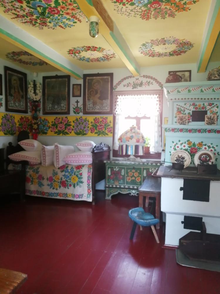 zdjęcie przedstawia izbę, w której stoi piec, komoda, łóżko z poduszkami, na ścianach wiszą obrazy