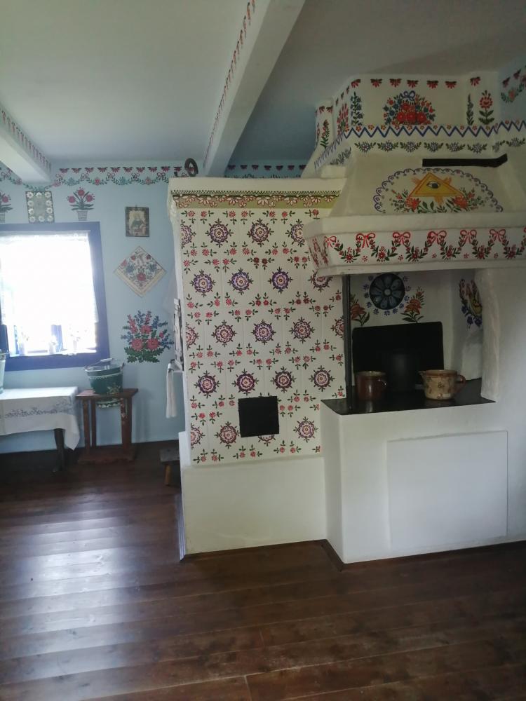 zdjęcie przedstawia izbę, w której stoi piec, dwa naczynia, stół, stołek a na nim umieszczone jest wiadro, ściany przyozdobione są folkowymi wzorami