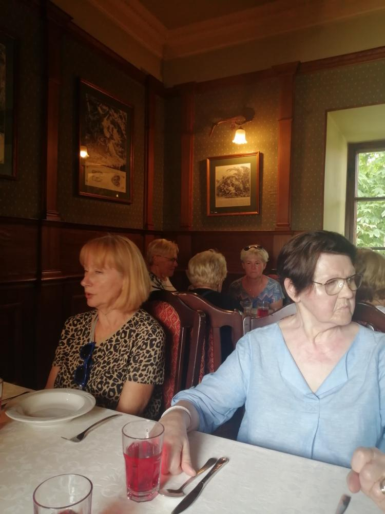 zdjęcie przedstawia kobiety siedzące przy stole, na którym znajdują się talerze i sztućce