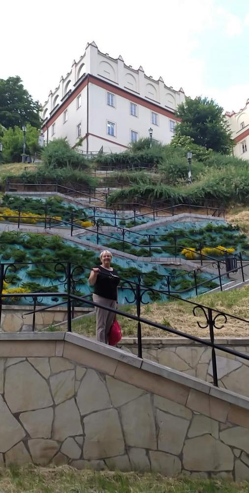 zdjęcie przedstawia katedrę na wzgórzu, schody do niej prowadzące i kobietę