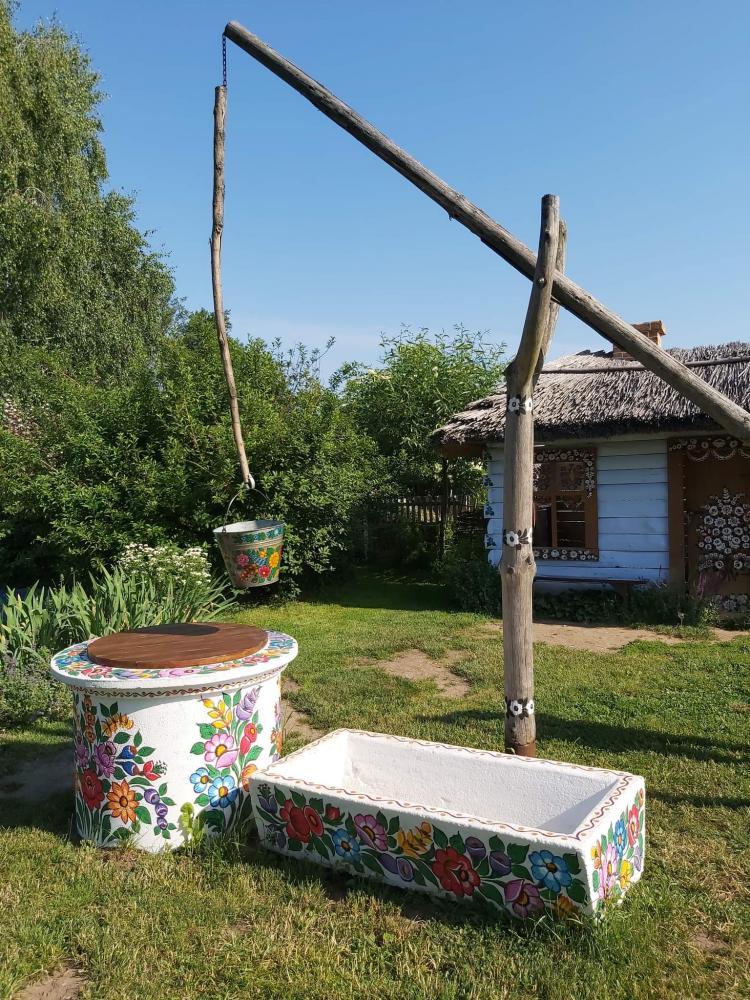 zdjęcie przedstawia studnię przyozdobioną folkowymi wzorami, a za nią znajduje się chata