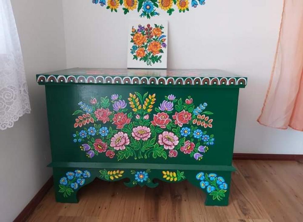 zdjecie przedstawia zielona komodę przyozdobiona folkowymi wzorami