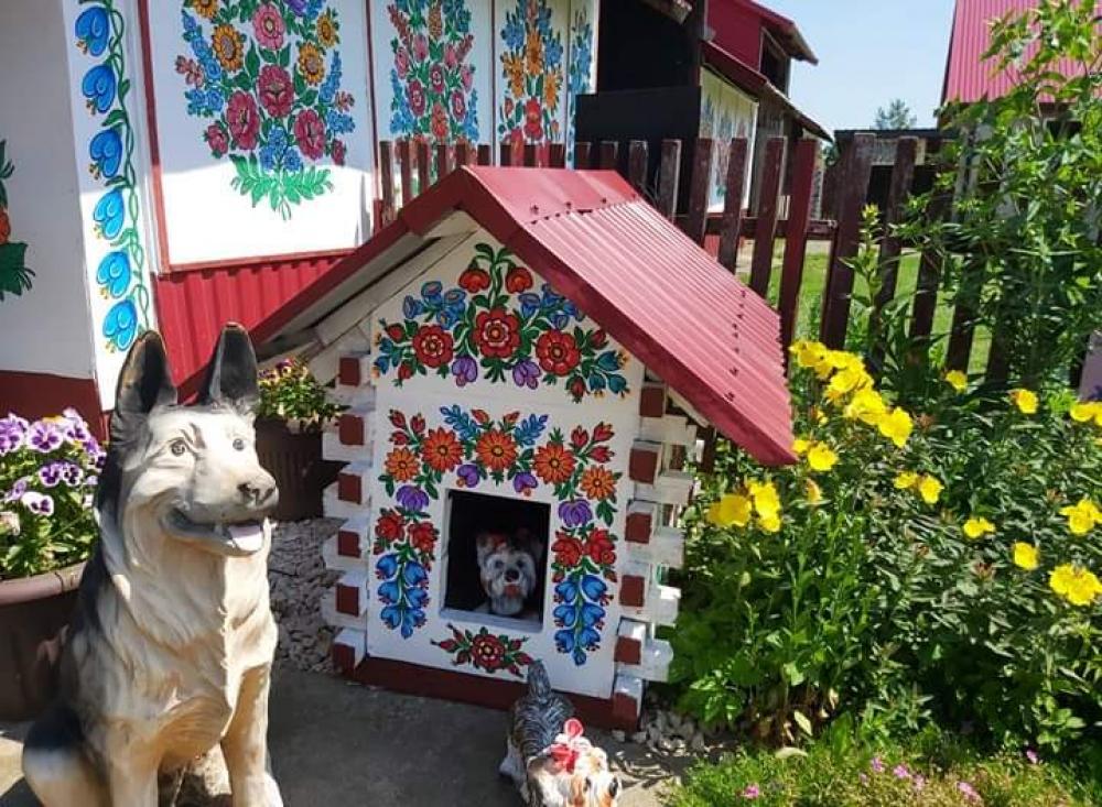 zdjęcie przedstawia figurkę psa i budę z tyłu znajduje się kawałek chaty, przedmioty ozdobione są folkowym wzorem