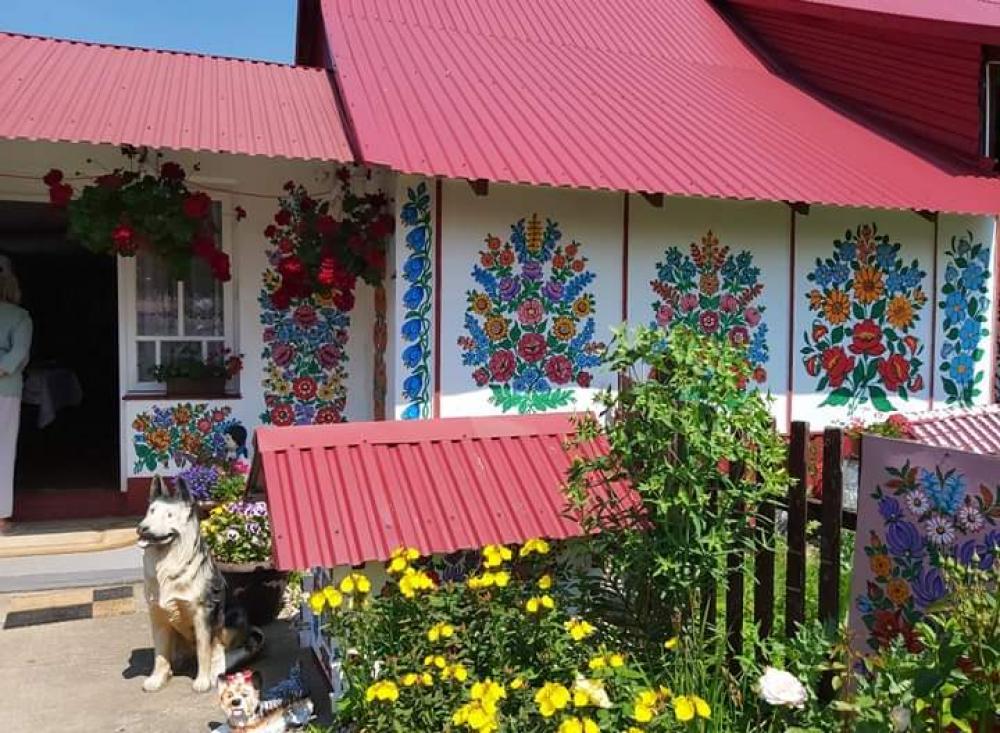 zdjecie przedstawia figurke psa, budę i kawałek chaty przyozdobionej folkowymi wzorami