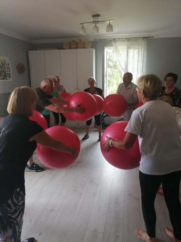 Seniorzy ćwiczący z dużymi piłkami w pomieszczeniu