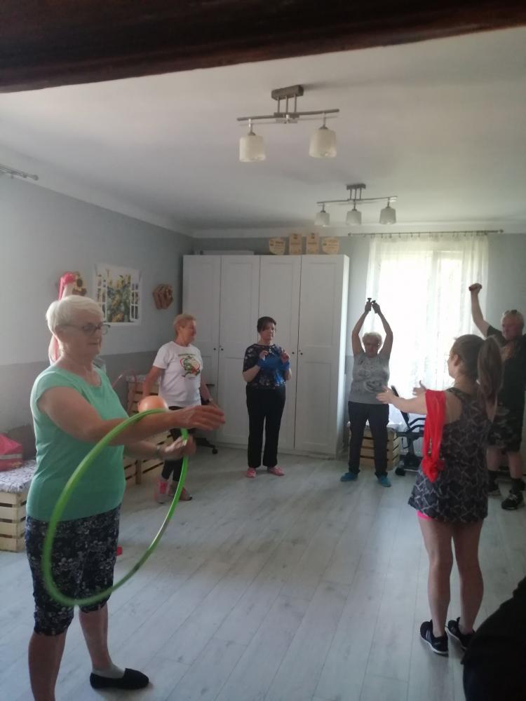 Seniorzy ćwiczący z hula hop, szarfami, małymi piłkami oraz ciężarkami do ćwiczeń   w Klubie Seniora.