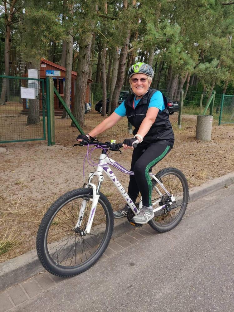 Seniorka  jadąca na rowerze.