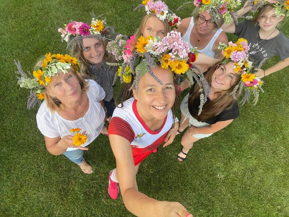 Kobiety z  kolorowymi wiankami z żywych  kwiatów i ziół na głowie.