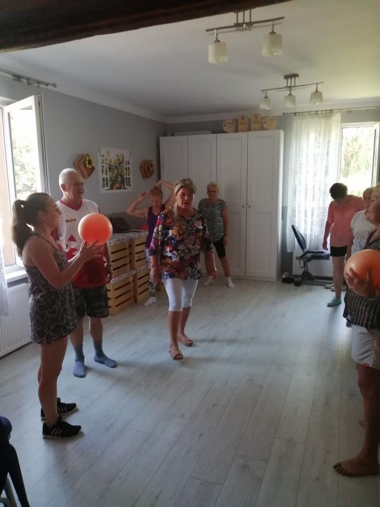 Seniorzy ćwiczący z piłkami  w Klubie Seniora.