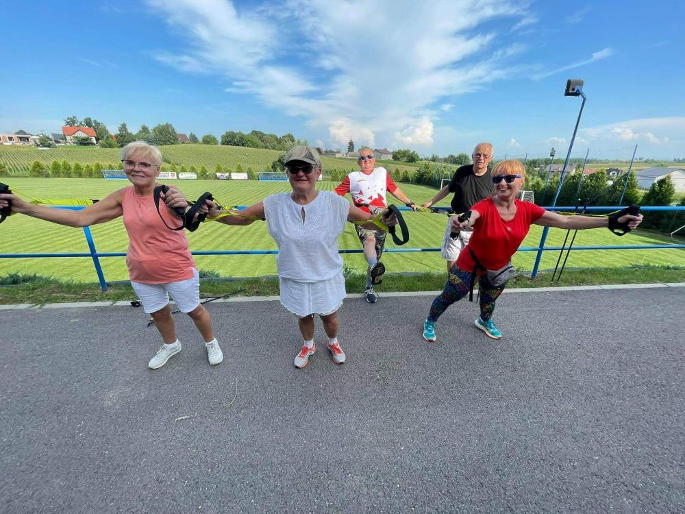 Seniorzy ćwiczący z szarfami przed boiskiem sportowym w Kocmyrzowie. ( 3 kobiety i 2 mężczyzn)
