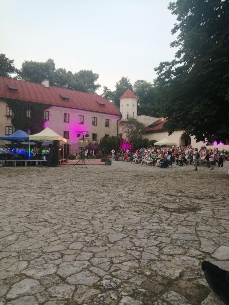 Seniorzy uczestniczący   w koncercie Orkiestry Dętej z Cianowic  przed Zamkiem w Piaskowej Skale.