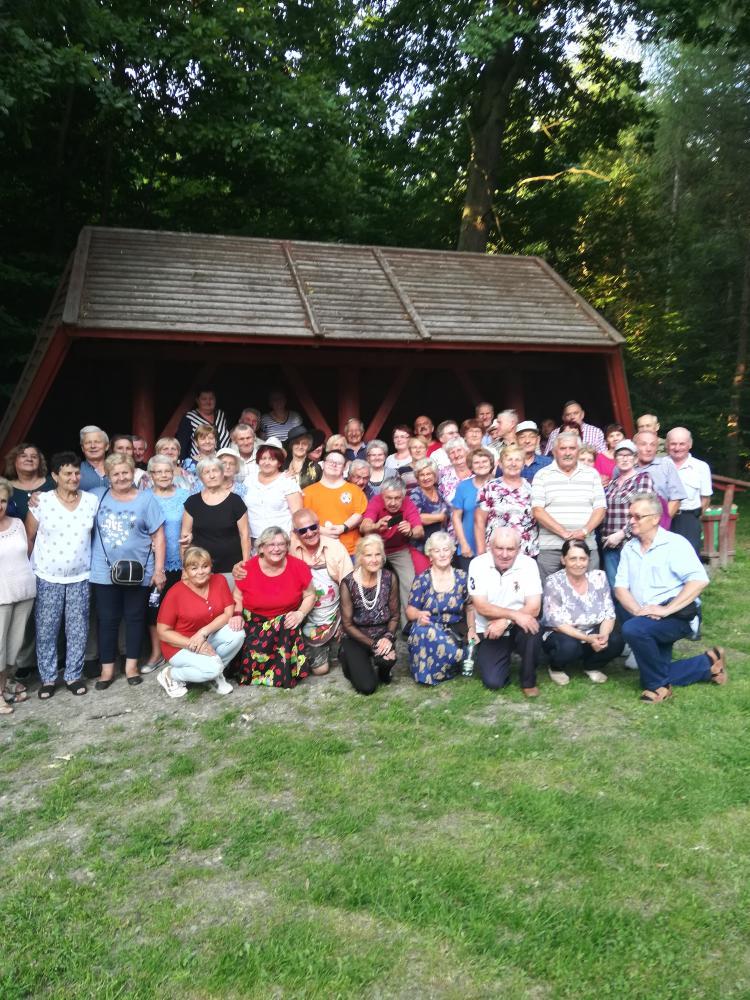 Spotkanie integracyjne seniorów w Lesie w Goszczy. Seniorzy stojący w grupie.