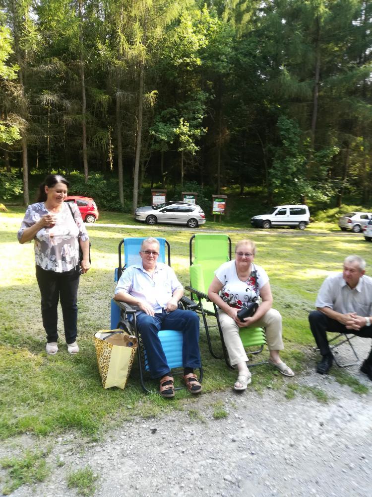 Seniorzy siedzący na polowych krzesłach.