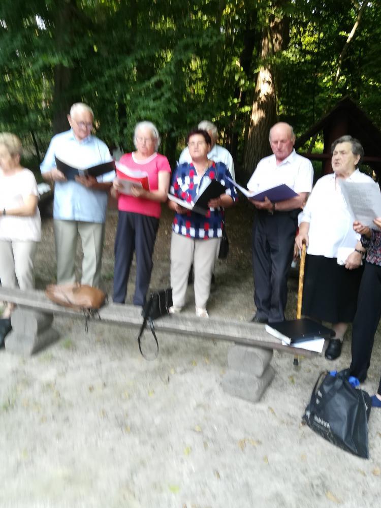 Seniorzy stojący ze śpiewnikami.