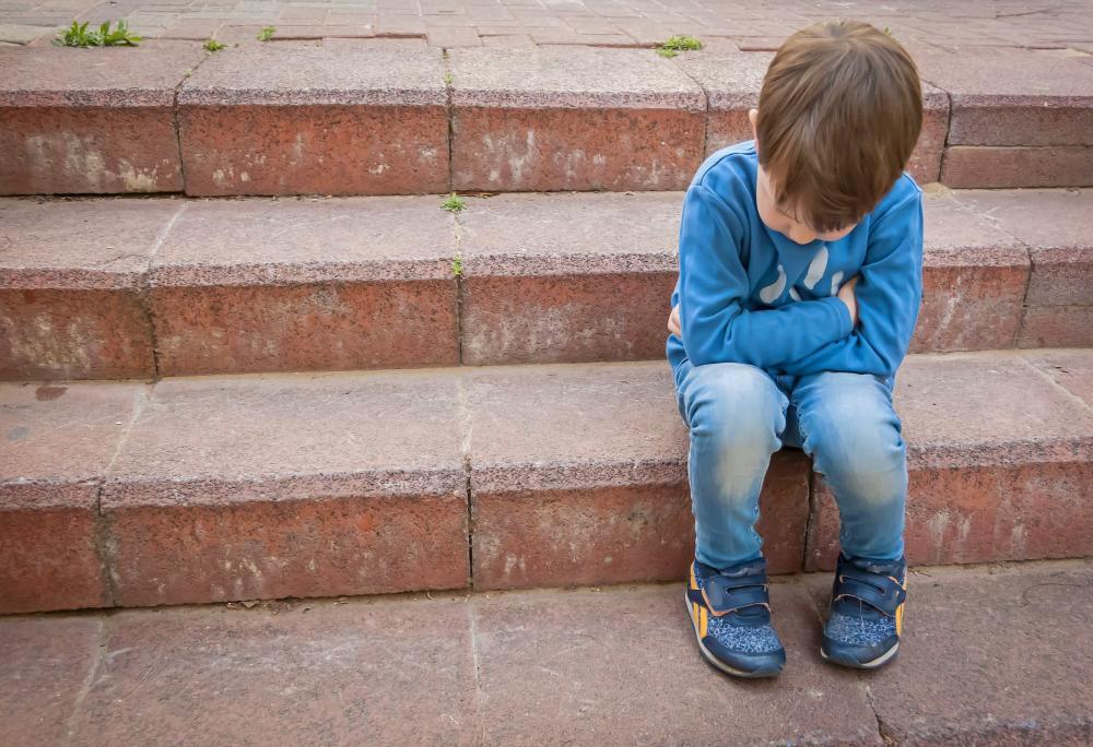 Mały chłopiec siedziący na schodach.