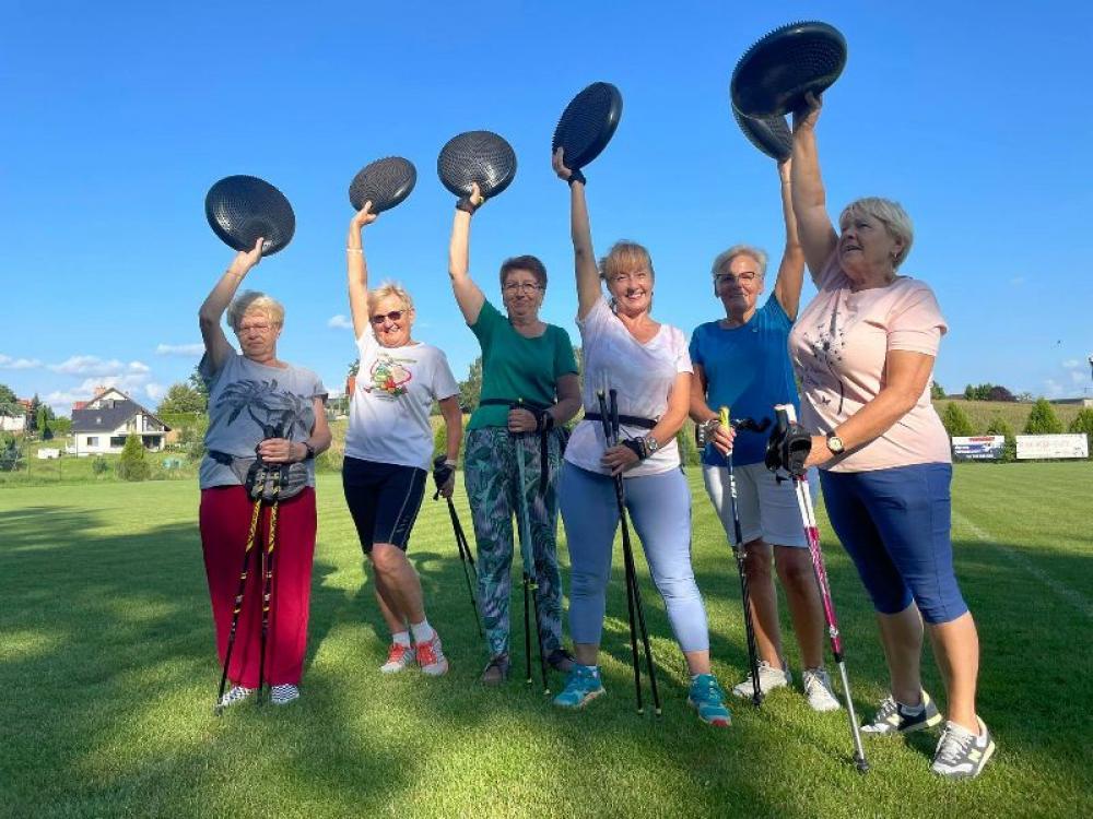 Śześć kobiet ćwiczących na boisku sportowym  z dyskiem balansowym.