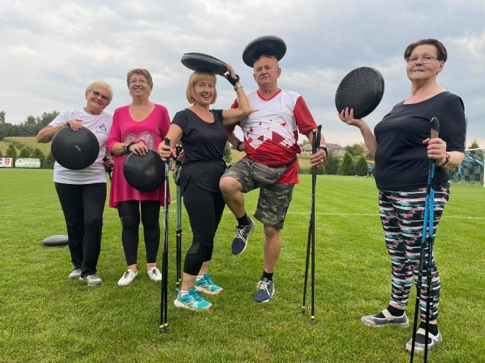 Sześć kobiet ćwiczacych na boisku sportowym z dyskiem balansowym .  Drugie ujęcie.