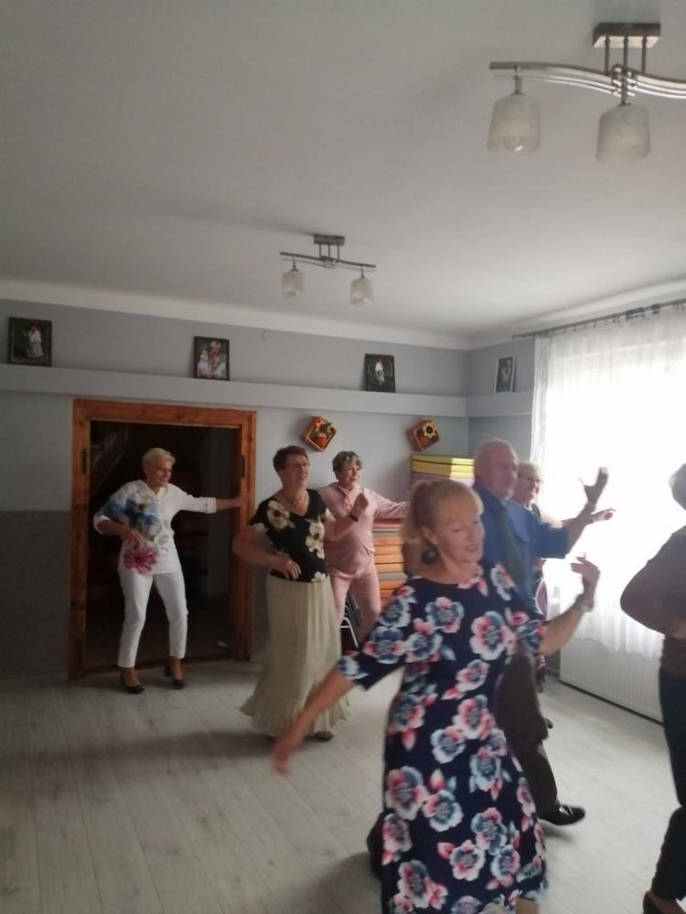 Zjecie na którym  widać seniorów uczących się tańca.  Zajęcia odbywają się w Klubie Seniora.
