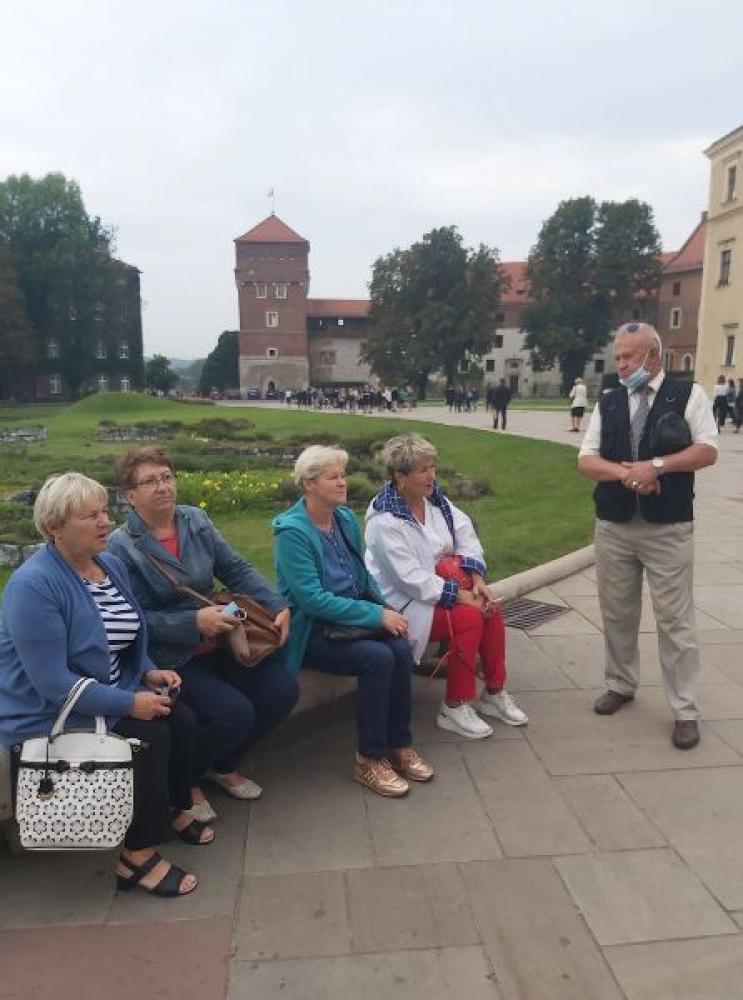 Na zdjęciu widać cztery kobiety siedzące na ławce oraz jednego mężczyznę  stojącego  tuż obok. W dali widać część Zamku Królewskiego w Krakowie