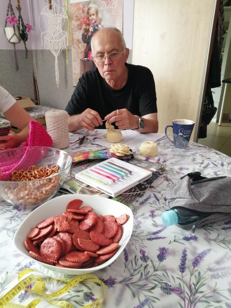 Na zdjęciu starszy mężczyzna, siedzący przy stole i szydełkujący.